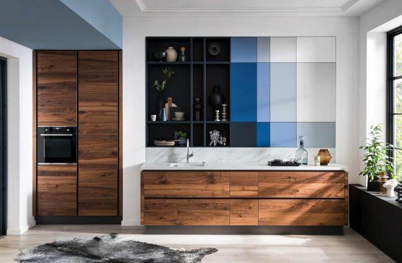 Grifflose Häcker Küche mit Nussbaumfronten und blauen Aktzenten